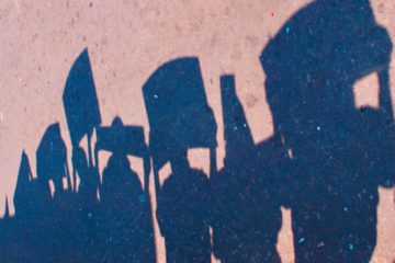 File: The silhouettes of activists holding signs seen in shadow on pavement. (Modified from Flickr / Vikalpa)